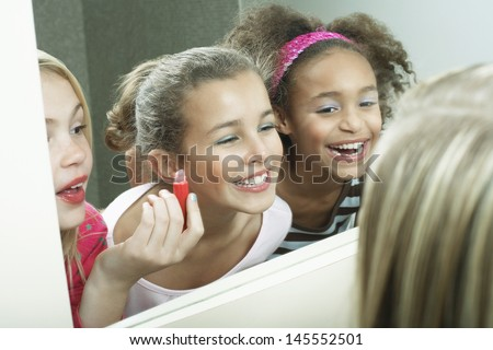 Closeup of three happy girls putting on makeup and lipgloss - stock photo