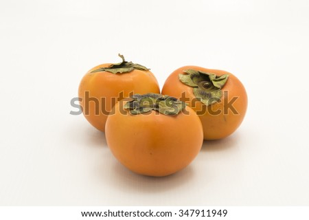 Closeup of three persimmon fruits.  Isolated on white background..