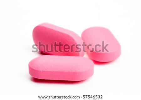 closeup of three pink pills - stock photo