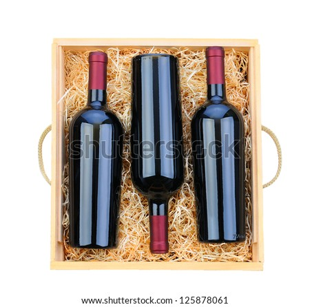 Closeup of three red wine bottles in a wooden case with packing straw. Overhead shot on a white background. - stock photo