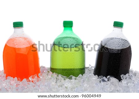 Closeup of three, two liter soda bottles in a large party style ice bucket. Only top half of bottles are visible. Lemon lime, orange and cola sodas over white. - stock photo