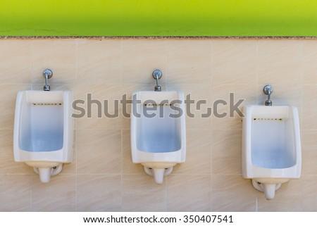 Closeup of three white ceramic urinals in men's bathroom.Urinal designed for the children. - stock photo