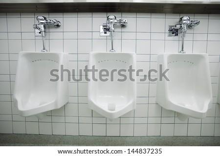 Closeup of three white urinals in men's bathroom - stock photo