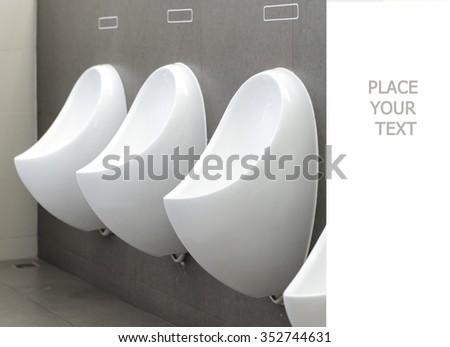 Closeup of three white urinals in men's bathroom, design of white ceramic urinals for men in toilet room - stock photo