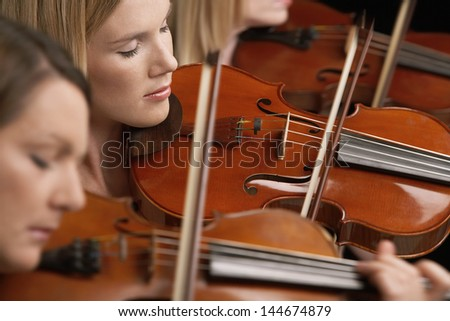 Closeup of three women playing violins in musical group - stock photo