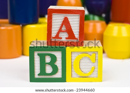 "Closeup of three wooden alphabet blocks in a pyramid spelling ""abc"""