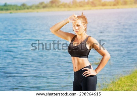 Closeup of tired young fitness woman in black sportswear standing outdoors by the lake on sunny summer day wiping her forehead relaxing after running. Horizontal, medium retouch, vibrant colors. - stock photo