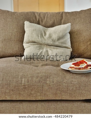 Closeup of toast with jam on plate on sofa