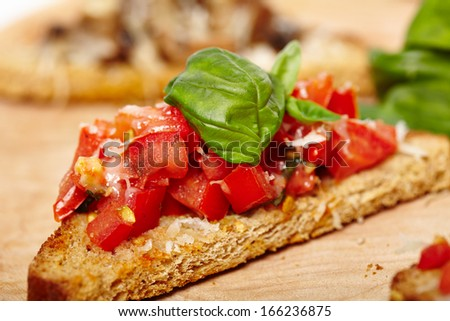 Closeup of tomato bruschetta in the foreground decorated with leaves of basil and parmesan and mushroom bruschetta in the background, selective focus - stock photo