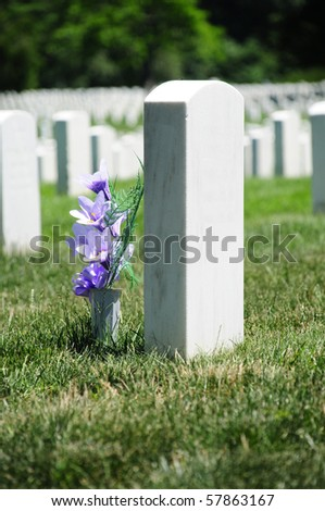 Closeup of tombstone with purple flowers at Arlington National Cemetery - stock photo