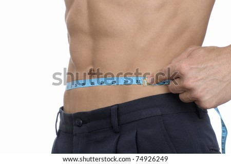 Closeup of topless man measuring his waist in inches - stock photo