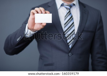 Closeup of torso of confident business man wearing elegant suit and mobile phone at pocket - stock photo