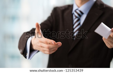 Closeup of torso of confident business man wearing elegant suit sharing his blank business card - stock photo