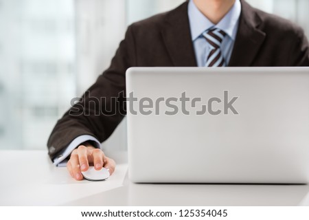 Closeup of torso of confident business man wearing elegant suit working with his laptop at office - stock photo