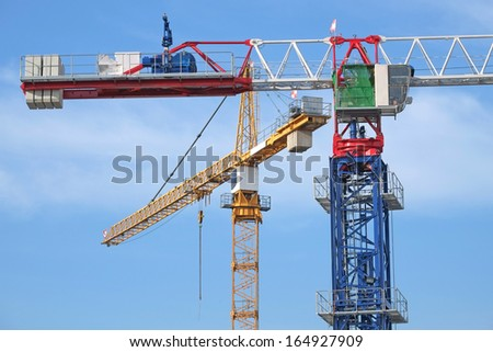 Closeup Of Tower Cranes At A Construction Site - stock photo