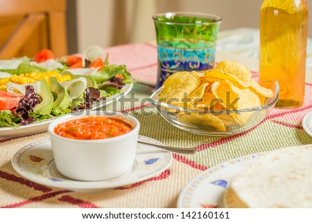 Closeup of traditional mexican food in a table, with  a bowl of nachos, spicy sauce, a plate of tortillas and fresh salad - stock photo