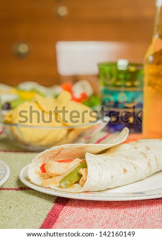 Closeup of traditional mexican food in a table, with a plate of chicken fajita, fresh salad and a bowl of nachos - stock photo