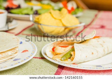 Closeup of traditional mexican food in a table, with a plate of chicken fajita, tortillas, fresh salad and a bowl of nachos - stock photo