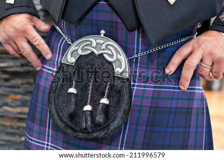 Closeup of traditional Scottish male ceremonial outfit. Man wearing blue tartan  kilt with beautiful fur and silver sporran. - stock photo