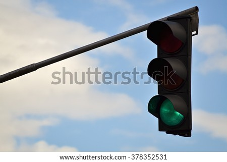 Closeup of traffic light and cloudy sky in the background