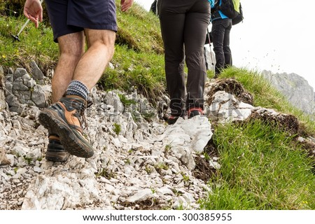 Closeup of trekking shoes. Hikers ascending a rocky road.