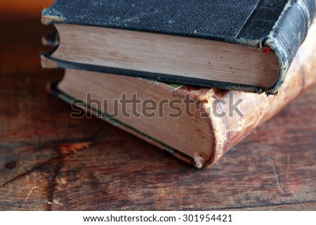 Closeup of two ancient books on old wooden background - stock photo