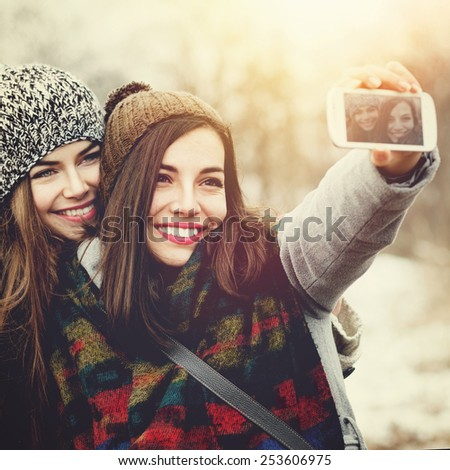 Closeup of two beautiful Caucasian teenage girls with knit beanie hats taking a selfie with smartphone outdoors in winter. Square format images, retouched, instagram look, filter applied. - stock photo