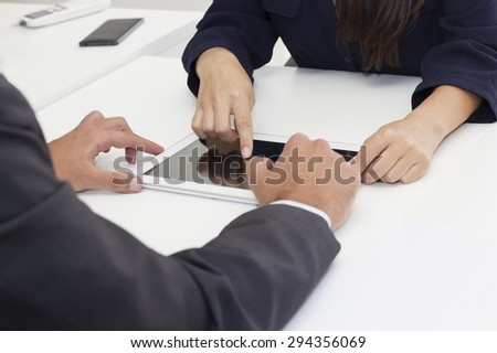 Closeup of two business person hands working on a digital tablet . - stock photo