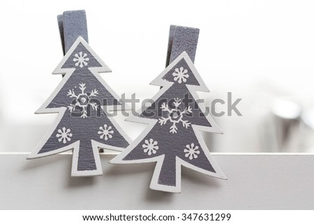 Closeup of two christmas tree shaped clothespins in the foreground. - stock photo