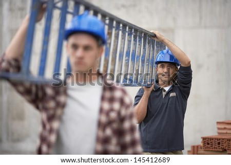 Closeup of two construction workers carrying ladder - stock photo