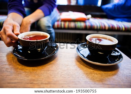 Closeup of two cups of tea on wooden table with one being held by hand of woman sitting on cafe bench - stock photo