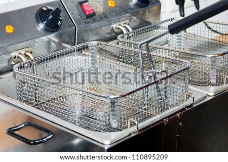 Closeup of two empty deep dirty fryers with shallow depth of field - stock photo