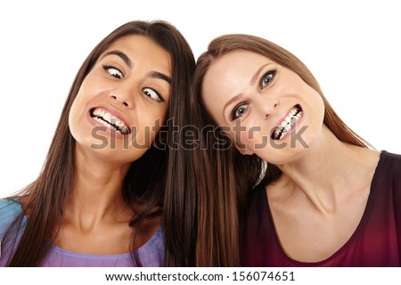 Closeup of two girlfriends making funny faces isolated on white - stock photo