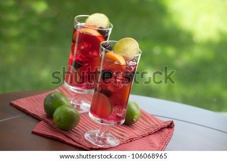 Closeup of two glass of Red Sangria - apricot, lime and blackberry - on outside table. - stock photo