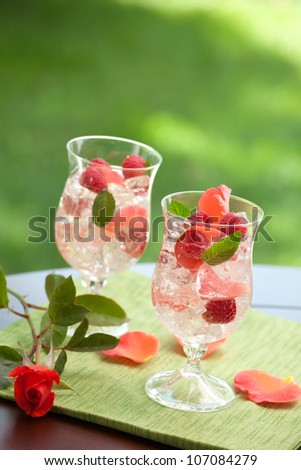 Closeup of two glass of white raspberry rose Sangria on outside table. - stock photo