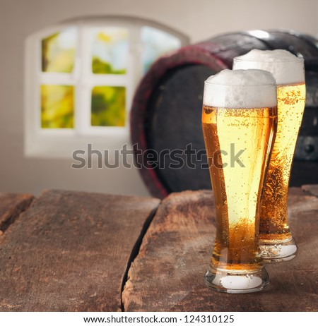 Closeup of two glasses of tasty fresh beer on a wooden table - stock photo