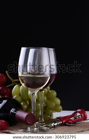 Closeup of two glasses with red and white wine standing on burlap napkin near green and red grapes bunches and lying new uncorked bottle and corkscrew on black background copyspace, vertical picture - stock photo