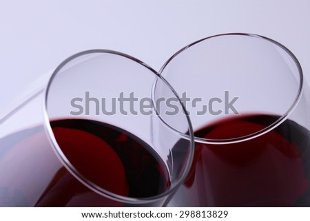 Closeup of two glasses with red dessert grapes wine clinking in toast standing close to each other with thin rims isolated on light grey background, horizontal picture - stock photo