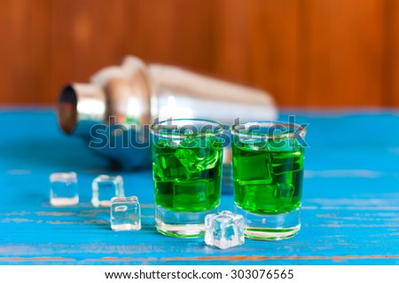 Closeup of two green absinthe alcohol shots with ice cubes and shaker on a light wooden background - stock photo