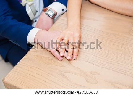 closeup of two hands of young adults with wedding rings