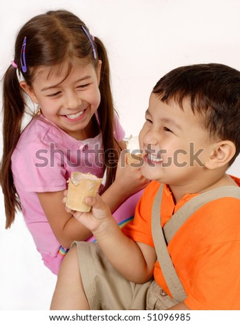 Closeup of two happy children eating ice cream, looking toward each other - stock photo