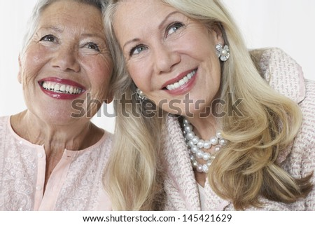 Closeup of two happy elegant senior women against white background