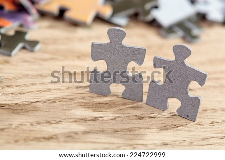 Closeup of  two jigsaw puzzle pieces on a table. Shallow depth of field