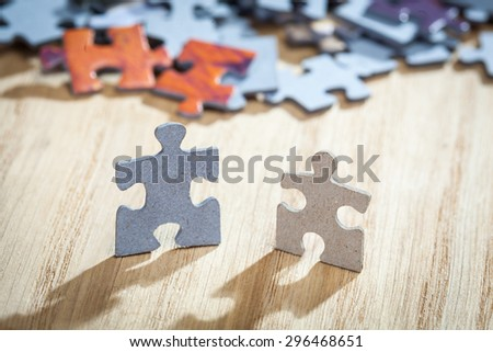 Closeup of two jigsaw puzzle pieces on table. Shallow depth of field - stock photo