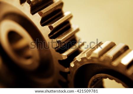 Closeup of two metal cog gears - stock photo