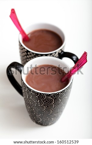 Closeup of two mugs of hot chocolate with red plastic spoons on light surface - stock photo