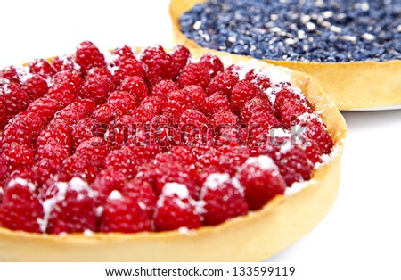 Closeup of two pies with blueberries and rasberries on white background - stock photo