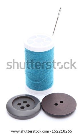 Closeup of two sewing buttons and spool of thread with needle. Isolated on white background - stock photo