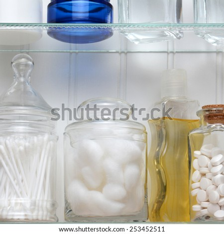 Closeup of two shelves of a medicine cabinet. A bottle of tablets, cotton balls and cotton swabs and assorted jars and bottles of soap and lotions. Square format. - stock photo