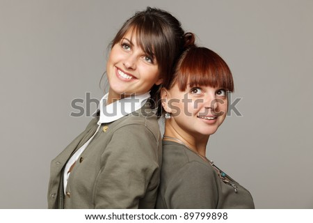 Closeup of two smiling girls standing back to back looking upwards, over grey background - stock photo